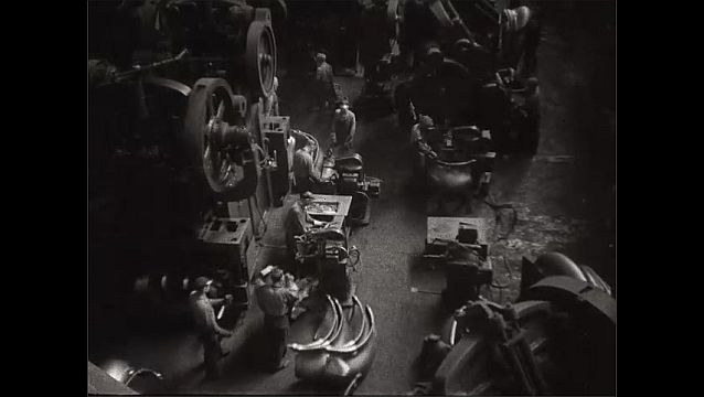 1940s: UNITED STATES: men lift metal from machine. Overhead view of production on factory floor.