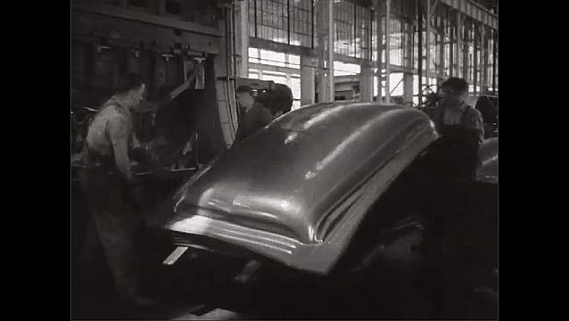 1940s: UNITED STATES: machinery presses down on metal. Men lift sheets of shaped metal from machine
