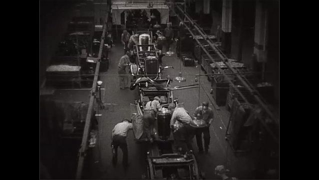 1940s: UNITED STATES: men attach exterior to motor cars in factory.