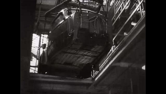 1940s: UNITED STATES: motor car on crane. Men lift exterior of car into position.