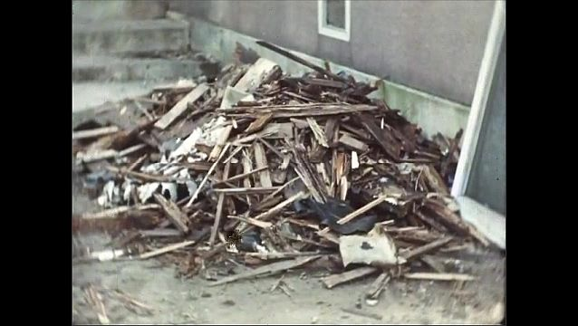 1930s: Run-down house with wood pile. Pile of splintered and damaged wood. House with holes and damage on exterior walls.