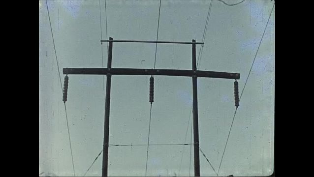 1930s: Large telephone poles and wires stretch into distance of rural landscape.