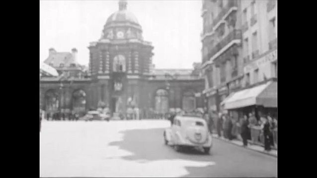 1940s: Statue of lion in front of Luxemburg Palace. Driving down road to Luxemburg palace with people lining sidewalks along way.