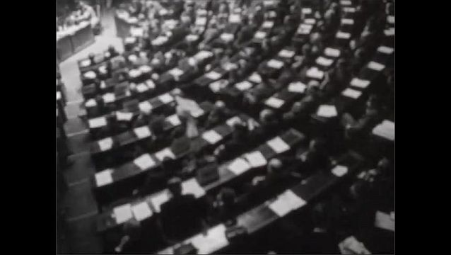 1940s: Secretary of State James F. Byrnes, stands at podium talking. Men sit in rows of desks in congressional assembly meeting room. Bombers fly over city. Bombers fly over land.