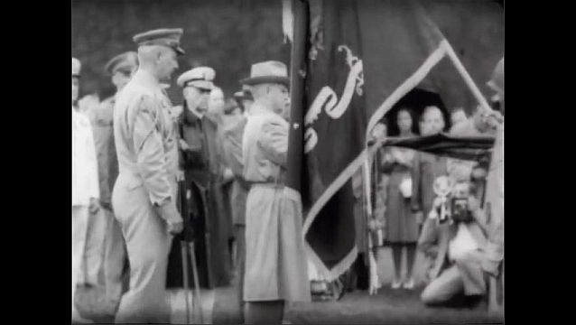 1940s: Soldiers stand in formation on field, holding flags. President Harry S. Truman wraps cloth around end of flag pole, doffs his hat and stands in group.