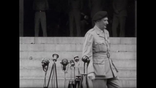 1940s: Bernard Montgomery and other officers walk down steps of building and stand in front of podium of microphones. Montgomery speaks into microphones.