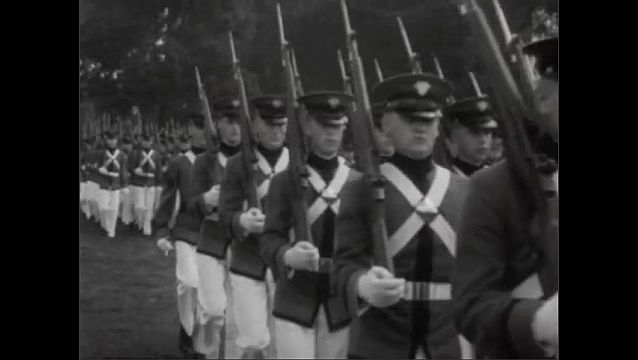 1940s: Bernard Montgomery and other officers walk across field. Officers stand in formation. Soldiers march in formation across field. Soldiers march, carrying flags.