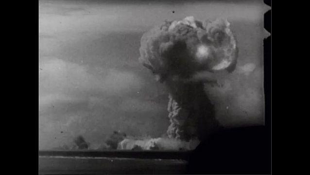 1940s: Movie cameras lined on dock of U.S.S. Appalachia. Man looking into movie camera. Atomic bomb explosion.