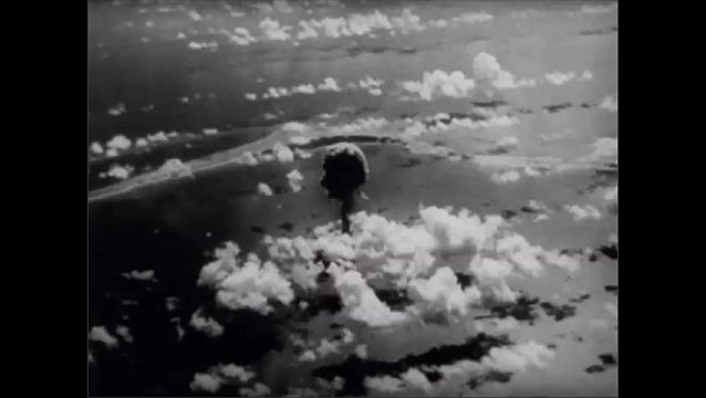 1940s: Large mushroom cloud from atomic bomb explosion, extends into sky. Mushroom cloud as seen from sky. Men on boat watch atomic bomb explosion.