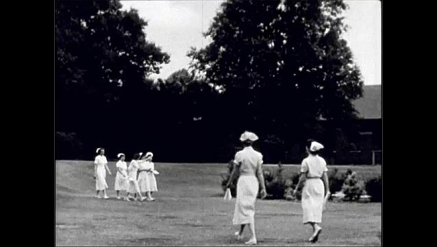 1940s: UNITED STATES: buildings and housing in hospital grounds. Nurses walk across grass at hospital. Nurse accommodation at hospital. Student nurse accommodation