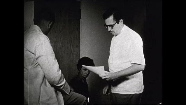 1940s: UNITED STATES: medical physicians examine female patient. Doctor signs paper. Court order admission to hospital. Judge in court. Man sits in court room.