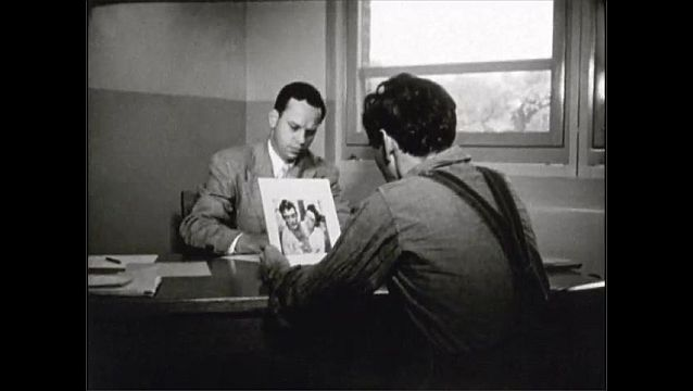 1940s: UNITED STATES: psychologist assesses patient. Man looks at photos.