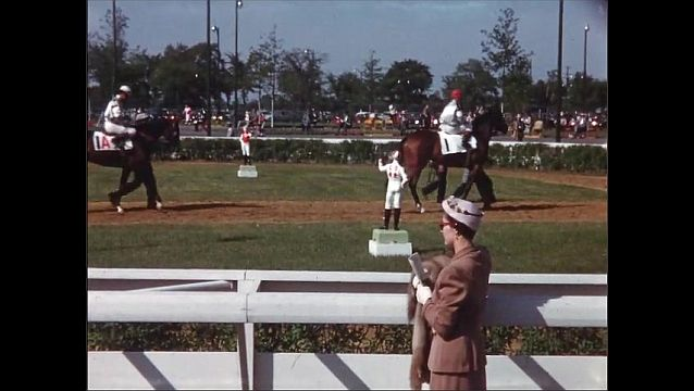 1960s: UNITED STATES: jockeys walk horses to start line of race. Lady watches horses from side.