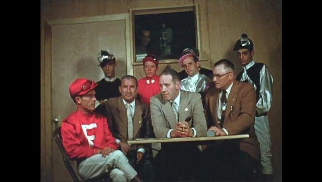 1960s: UNITED STATES: jockeys in meeting with men. Jockeys leave meeting