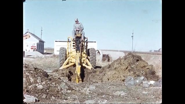 1930s: Small houses, field, man operates excavator, dumps bucket of soil onto pile, turns, digs hole deeper.