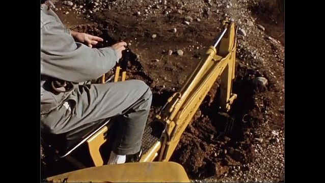 1930s: Field, man operates excavator, rotates arm, pushes levers, extends arm, digs soil from hole with bucket, dumps soil onto pile.