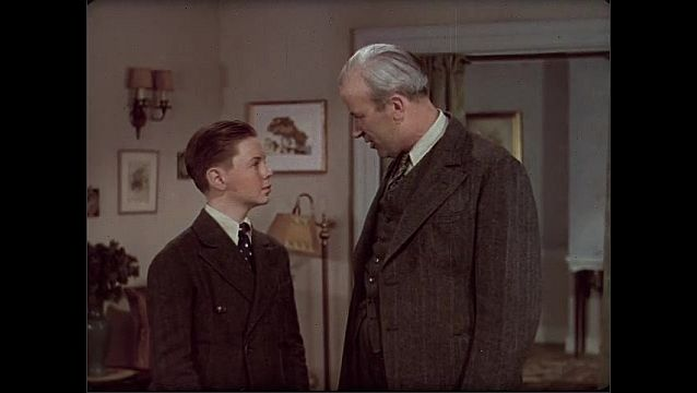 1930s: Living room, father puts arm around boy, talks, looks eye to eye, nods, looks determined. Boy's face lights up, smiles, looks excited, runs, yells across house.