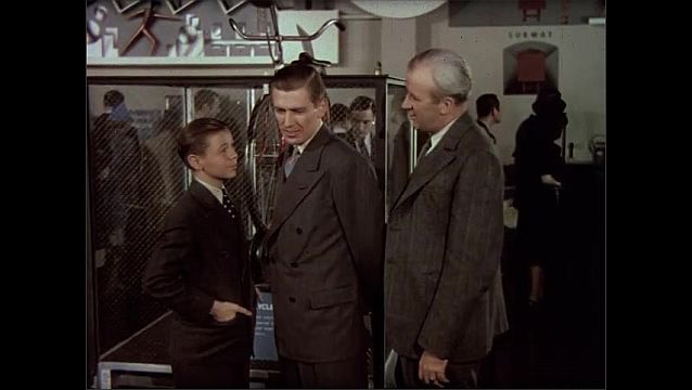 1930s: World's Fair, busy Westinghouse building, crowd mills, man gives tour to father, son, points, talks, smiles. Father stoops, looks at device. Son folds arms, asks question, looks skeptical.