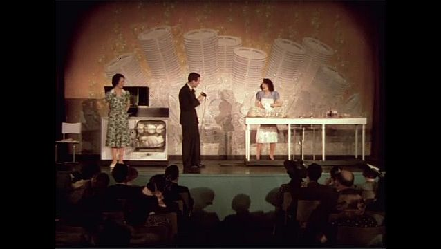 1930s: Man talks as woman washes dishes on stage. Woman opens dishwasher. Woman stops washing dishes. Man picks up dish.