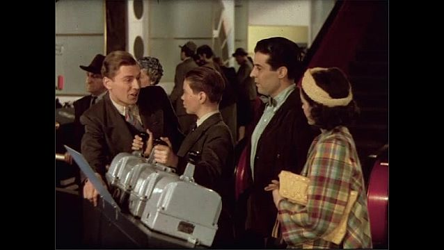 1930s: Man and woman talk. Boy touches levers. Woman touches man, and they walk away.
