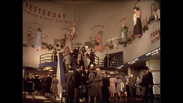1930s: Crowd in large room. People go up escalator and down steps.