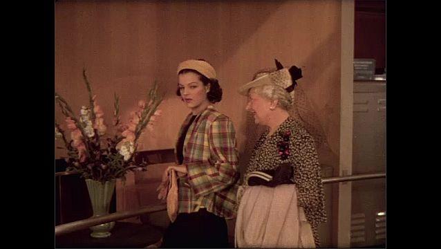 1930s: Women approach display of family room. Women speak.