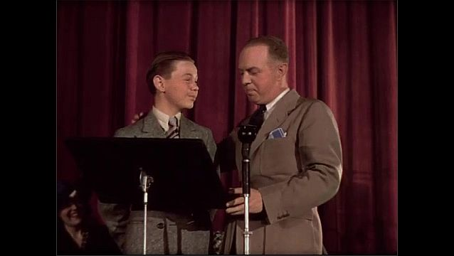 1930s: Man and boy stand on stage, talk.