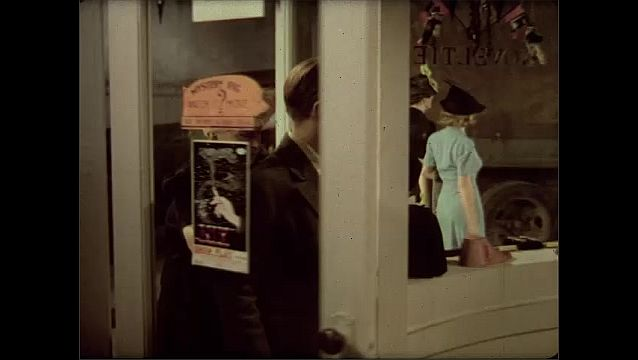 1930s: Woman and boy look at store display through window, walk into store, talk to man behind counter.