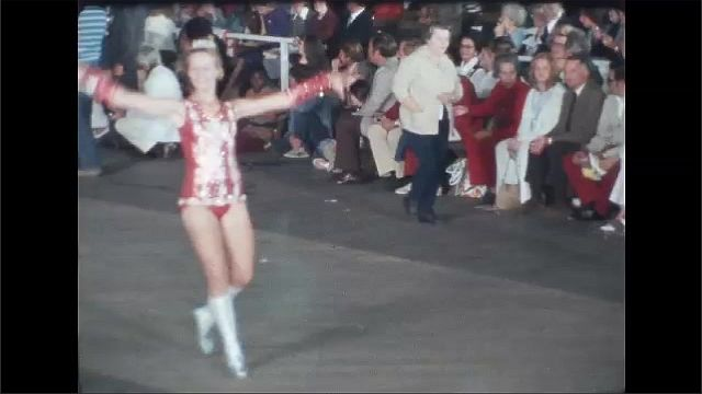 1970s: Cheerleaders march and wave batons in parade. Pageant winner waves from elaborate parade float. Girls wave batons and lead marching band through streets.