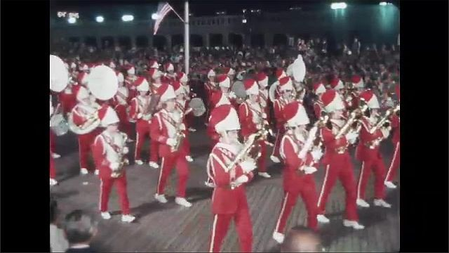 1970s: Men and women play instruments in marching band. Women of color guard wave flags and march in parade.