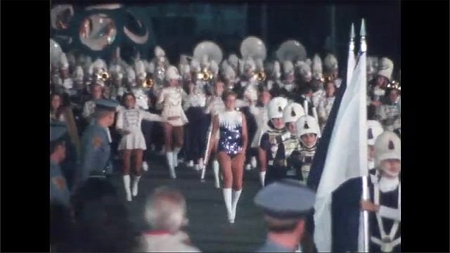1970s: Women in crowns and bikinis wave from decorated float. Marching band plays instruments in parade. Women dance with batons in parade.