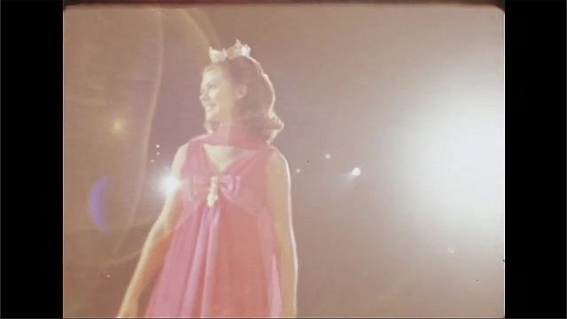 1970s: Woman gesticulates and sings on stage. Woman wears crown and dress on stage. Audience applauds woman in crown.