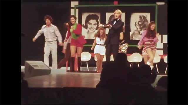 1970s: Women walk runway wearing sashes and gowns. Men and women sing and dance on stage. Woman sits in chair and plays banjo on stage.