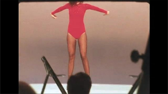 1970s: Woman in leotard performs splits between two chairs. Woman in leotard flips and performs on stage. Woman in dress sings and performs near table on stage.