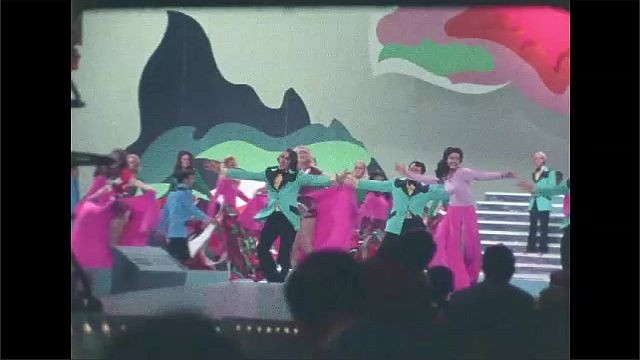 1970s: Men and women dance and sing on stage. Broadcast cameras point at performers on stage.