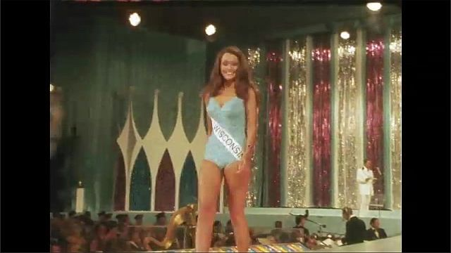 1970s: Women in sashes and swimwear walk on stage runway.