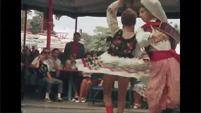 1960s: Man and woman in traditional Polish costumes dance at fairgrounds pavilion. Audience sits at tables and watches dancers.