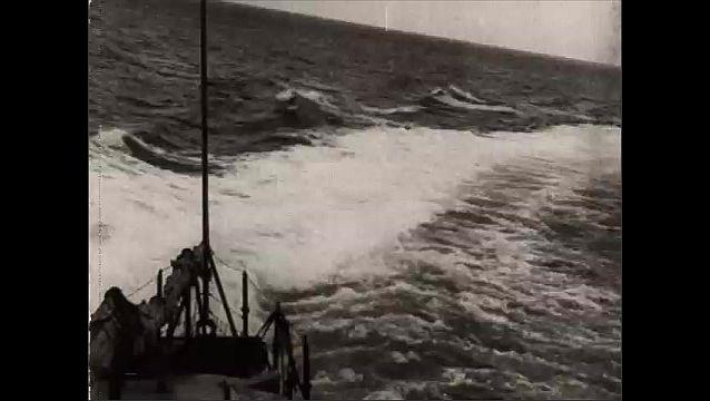 1940s: Man wavs flags on ship. Mne on ship load gun, fire gun. Tracking shot of water from ship. Lon shot,  ship fires guns. View of guns. Men load gun on ship.
