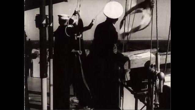 1940s: Views of battleships firing guns. Men raise flag on ship. Low angle, flags raising. View of ship,