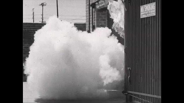 1940s: Man working by washer tank. Man turns valve, walks away. Explosion in doorway. Smoke exits from roof vent. Smoke in doorway. Close up, flames burn latch. Building burning. Door closing.