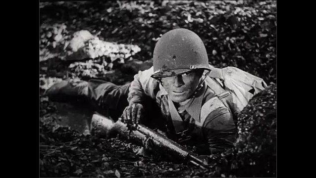 1940s: Soldier on ground. Hand pulls explosive from boot. Soldier on ground with gun. Hands with explosive. Soldier struggles with gun. Soldier throws explosive. Soldier on ground.