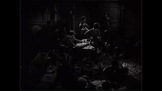 1940s: Close up of soldier. Soldiers in barn, lights go out. Soldier sits up. Soldier enters. Soldiers stand. Soldier picks up pieces of gun from table.