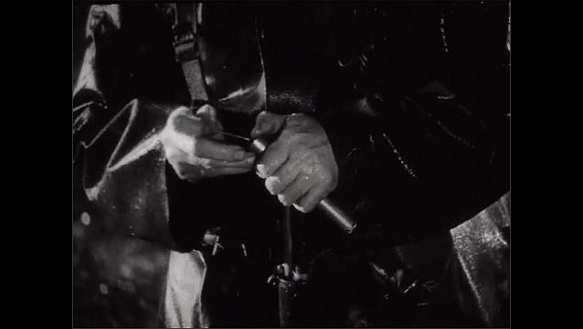 1940s: Close up, hands pour oil in gun barrel. Soldier reaches in bag. Hands with gun, hand takes item from bag.