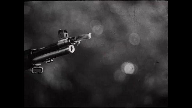 1940s: Soldier whistles, points gun. Soldier kneels, points gun. Pan across gun. Close up, soldier aiming gun. Close up, hand on gun. Soldier puts down gun.