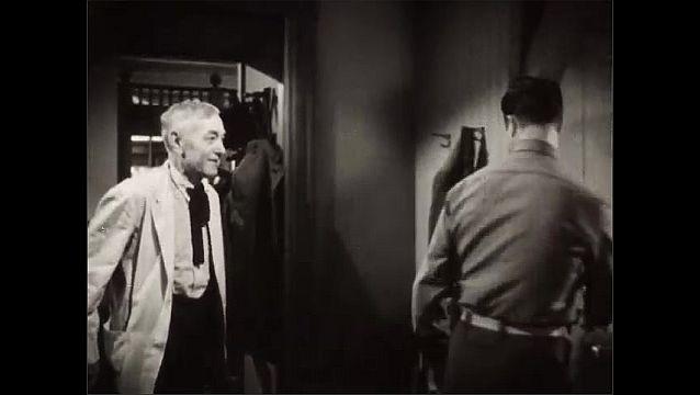 1940s: Man undressing in hallway, man enters, men talk, men walk into room, man hands man case, man opens case.