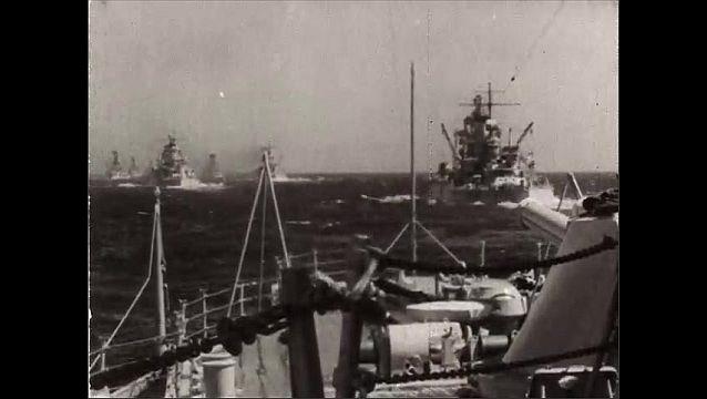 1940s: Nose of ship pushing through water. View from ship, fleet of battleships on water. Ships sailing.