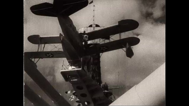 1940s: Low angle, airplane on ship. Front of plane. Panning shot, plane takes off from ship. Pan, plane taking off.