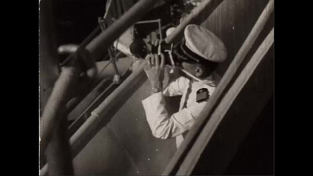 1940s: Views of battleships at sea. High angle, man on ship looks through binoculars. Man works signal light. Hand pushes lever. Close up, light shutters moving.