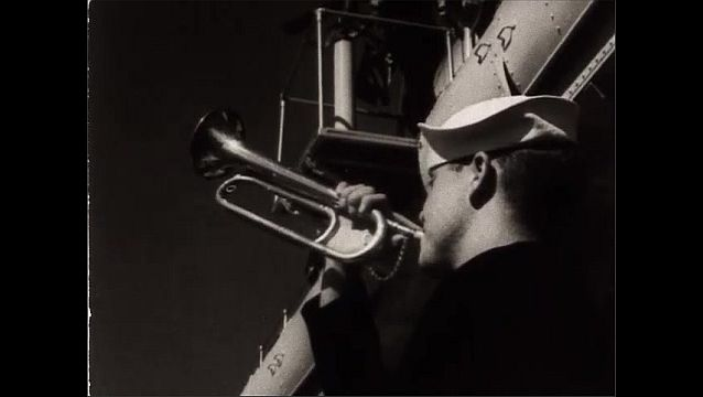 1940s: Views of battleships at sea. Man blows bugle. Close up, man with bugle. View of bell. Low angle, man run up ladder. Men tun up ladder onto deck. Feet on ladder.