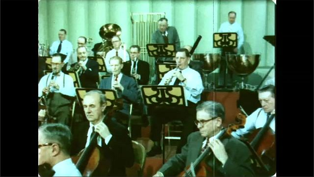 1960s: Men stand next to audio recording device, listen. Orchestra plays instruments. Conductor conducts.